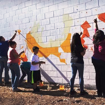 Lemon Grove Mayor Racquel Vasquez (right) is joined by several volunteers as they paint a breezeway off Lester Street near the 7800 block of Broadway on Saturday in Lemon Grove.